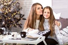 母亲和女儿在她的圣诞节的房子里 免版税库存照片