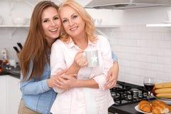 母亲和女儿在家一起过周末看照相机饮用的茶 库存照片