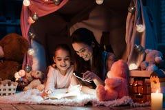 母亲和女儿在家晚了是与手电的阅读书在枕头房子里在晚上 免版税库存图片