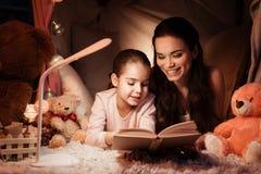 母亲和女儿在家晚了是阅读书在枕头房子里在晚上 免版税图库摄影