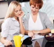 母亲和女儿在家读了杂志 免版税图库摄影
