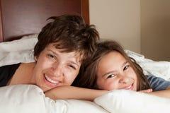 母亲和女儿在床上 免版税库存照片