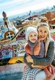 母亲和女儿在拥抱的巴塞罗那,当坐长凳时 免版税库存照片