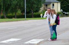 母亲和女儿在斑马交叉路前 库存图片