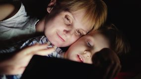 母亲和女儿在晚上在床上享受片剂谎言 面对面,愉快的一起概念 股票录像