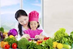 母亲和女儿在桌上的裁减菜 免版税库存照片