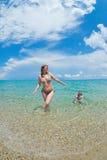 母亲和女儿在海沐浴 免版税库存图片