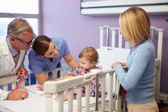 母亲和女儿在医院小儿科病区里  库存图片