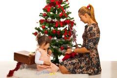 母亲和女儿在Xmas树前面 免版税图库摄影