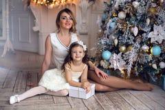 母亲和女儿坐在圣诞树的三年 免版税库存图片