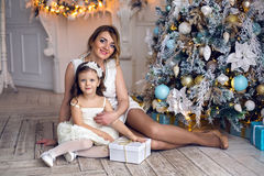 母亲和女儿坐在圣诞树的三年 库存图片