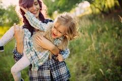 母亲和女儿坐在日落的领域 库存照片