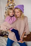 母亲和女儿坐大床 免版税库存图片