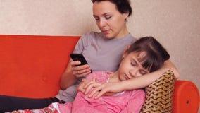母亲和女儿坐有机动性的长沙发 母亲看一个手机,女儿睡眠 股票录像