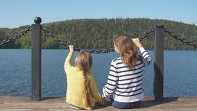母亲和女儿坐码头温暖的秋天天 股票视频