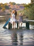 母亲和女儿坐码头 库存图片