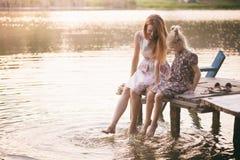 母亲和女儿坐码头 图库摄影