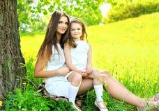 母亲和女儿孩子一起坐草在树附近在夏天 免版税库存图片