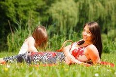 母亲和女儿小女孩有野餐在公园 免版税库存照片