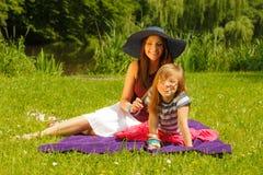 母亲和女儿小女孩有野餐在公园 图库摄影