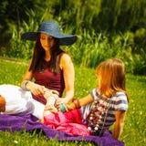 母亲和女儿小女孩有野餐在公园 免版税库存图片