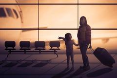 母亲和女儿带着手提箱在机场大厅里 库存图片