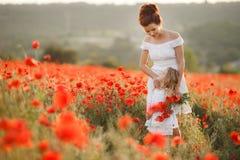 母亲和女儿开花的鸦片的领域的 免版税图库摄影