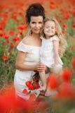 母亲和女儿开花的鸦片的领域的 库存照片