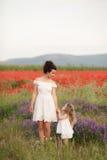 母亲和女儿开花的鸦片的领域的 免版税库存照片