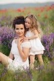 母亲和女儿开花的鸦片的领域的 免版税库存图片