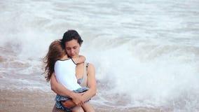 母亲和女儿拥抱亲吻在海海滩 影视素材