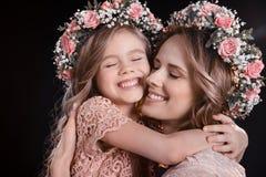 母亲和女儿拥抱在黑色的花卉花圈的 免版税库存照片