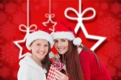 母亲和女儿拿着袋子棒棒糖的圣诞老人帽子的 库存图片