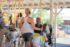 母亲和女儿旋转木马的 图库摄影
