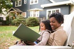 母亲和女儿有书的 免版税库存图片