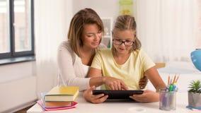 母亲和女儿有做家庭作业的平板电脑的 股票视频