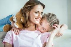 母亲和女儿有在家拥抱在沙发的玩具熊的 免版税库存照片