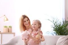 母亲和女儿有存钱罐的 图库摄影