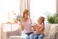 母亲和女儿有存钱罐的 免版税库存照片
