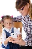 母亲和女儿有手机的 库存图片