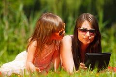 母亲和女儿有片剂个人计算机的在公园 免版税库存照片