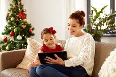 母亲和女儿有片剂个人计算机的在圣诞节 免版税库存照片
