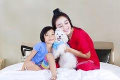 母亲和女儿有狗的在卧室 免版税库存照片
