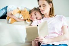 母亲和女儿有玩具熊一起阅读书的在沙发 免版税库存图片