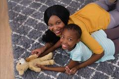 母亲和女儿有玩具熊的,当在家时说谎在地毯 免版税库存图片