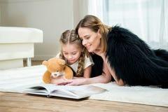 母亲和女儿有玩具熊阅读书的在地毯 库存图片