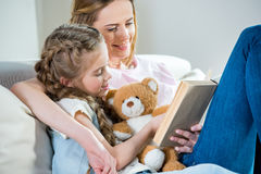 母亲和女儿有玩具熊阅读书的在沙发 图库摄影