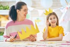 母亲和女儿有纸辅助部件的 免版税库存图片