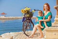 母亲和女儿有自行车的在海靠岸 免版税库存图片