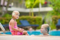 母亲和女儿有花的在耳朵后获得乐趣在水池边 库存照片